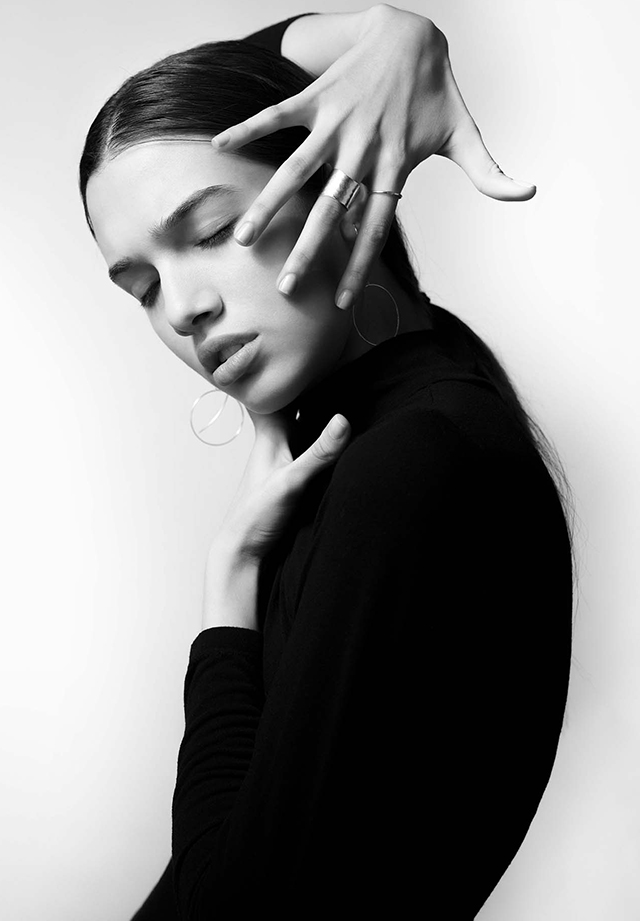 Black and white image with woman wrapping her fingers straight on her face