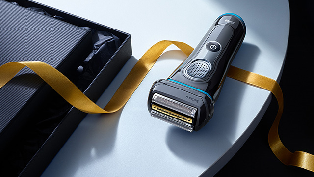 Blue shaver with gold ribbon floating around it