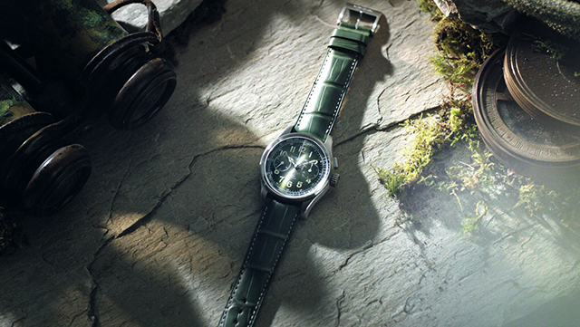 Watch with green strap band on a rock surface